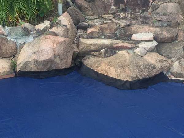 Pool cover on rock edge pool