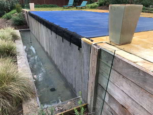 Blue leaf cover fitted to infinity edge pool